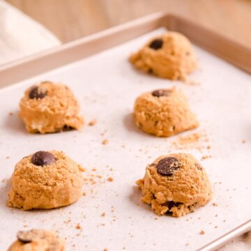 scooped smores cookie dough balls on a baking sheet with a chip and graham crumbs on top.
