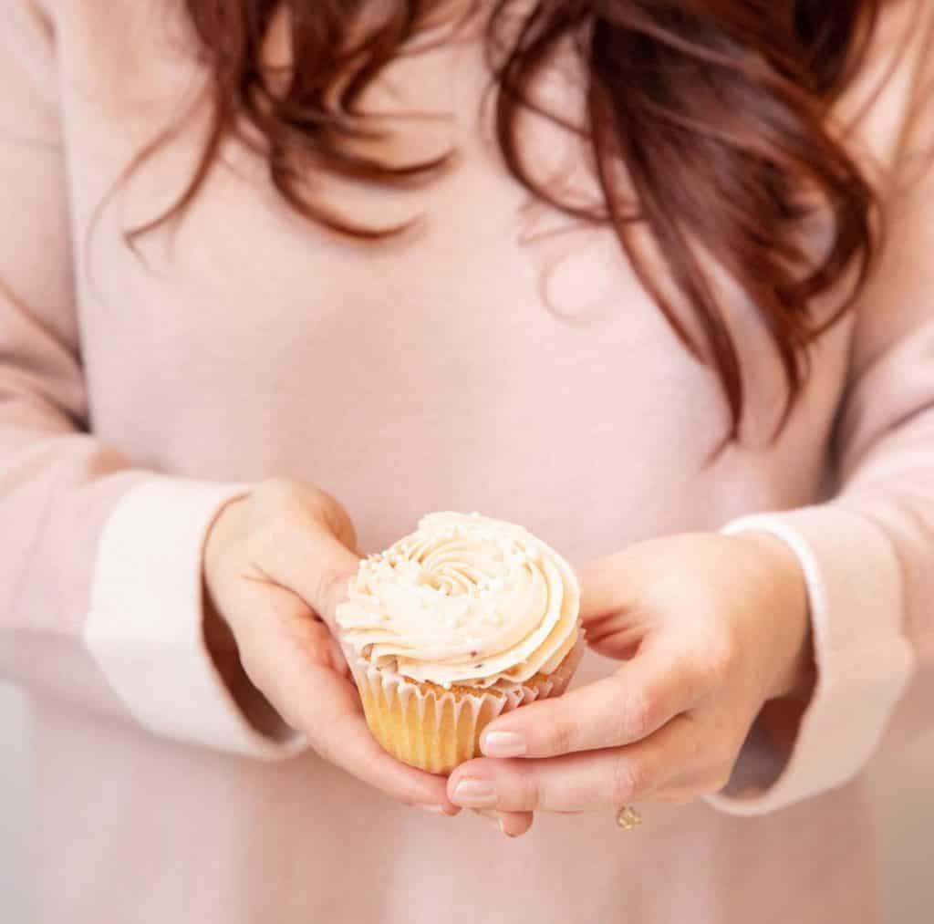 girl holding a jam-filled vanilla cupcake