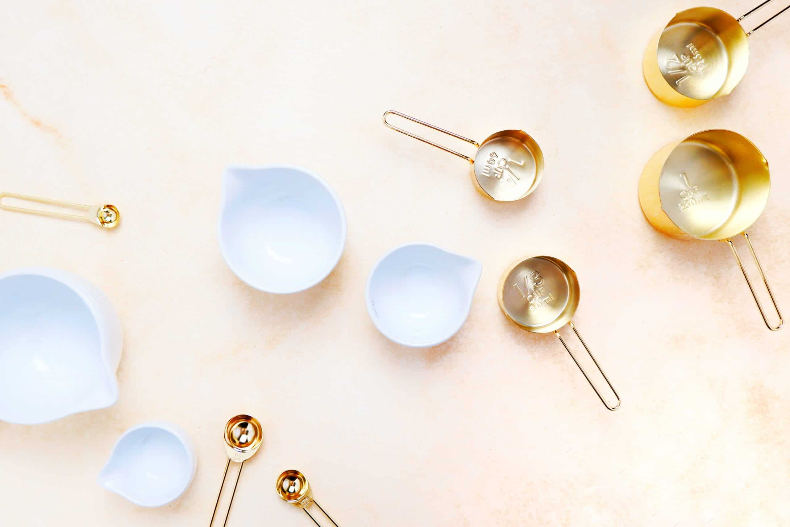 empty measuring cups in whilte and gold scattered on an orange backdrop.