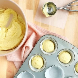 bowl of cupcake batter and cupcake being scooped into a pan