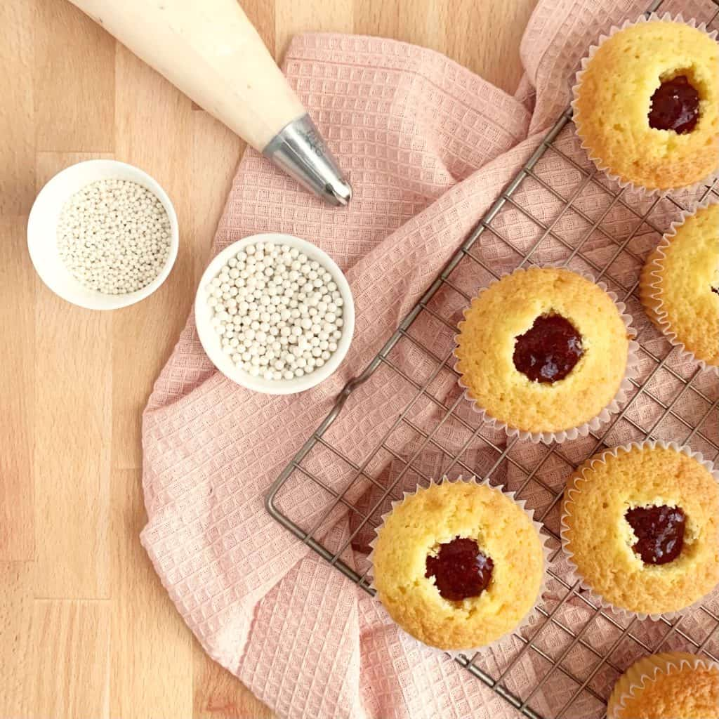 jam-filled cupcakes with a frosting bag and sprinkles