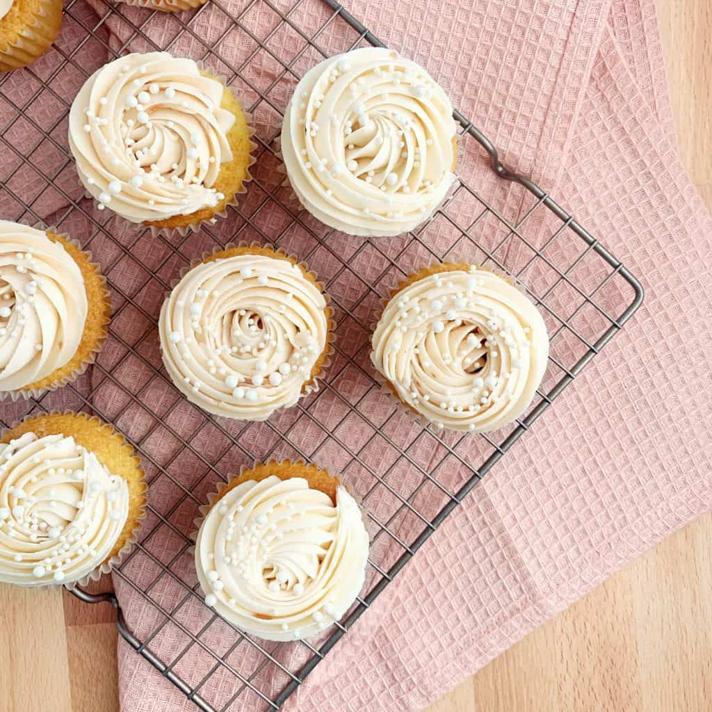 jam-filled vanilla cupcakes with a rosette and pearl sprinkles