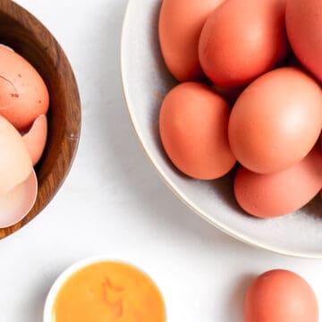 fresh eggs, whole eggs, egg whites, egg shells, and egg yolks in bowls