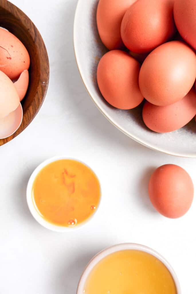 fresh eggs, whole eggs, egg whites, egg shells, and egg yolks in bowls