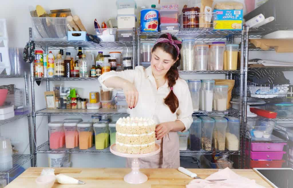 Jocelyn adding sprinkles to a rice krispie treat cake in the kitchen