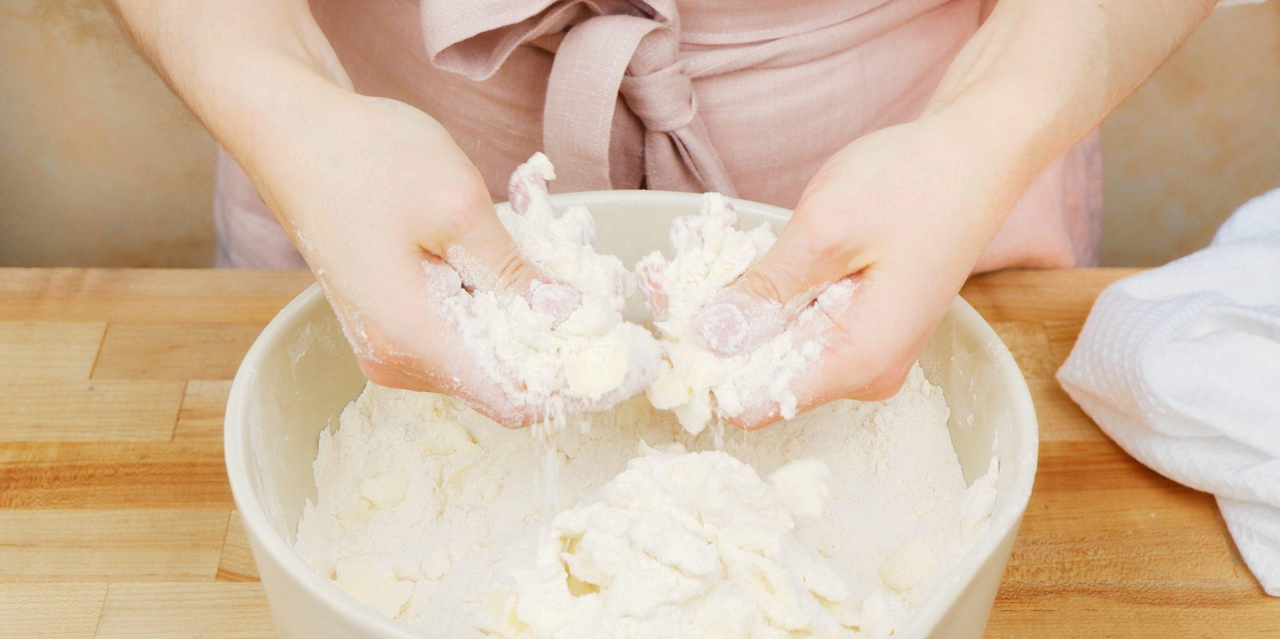 a baker's hands cutting butter into a bowl of flour