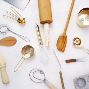 various tools used for baking scattered across a white surface
