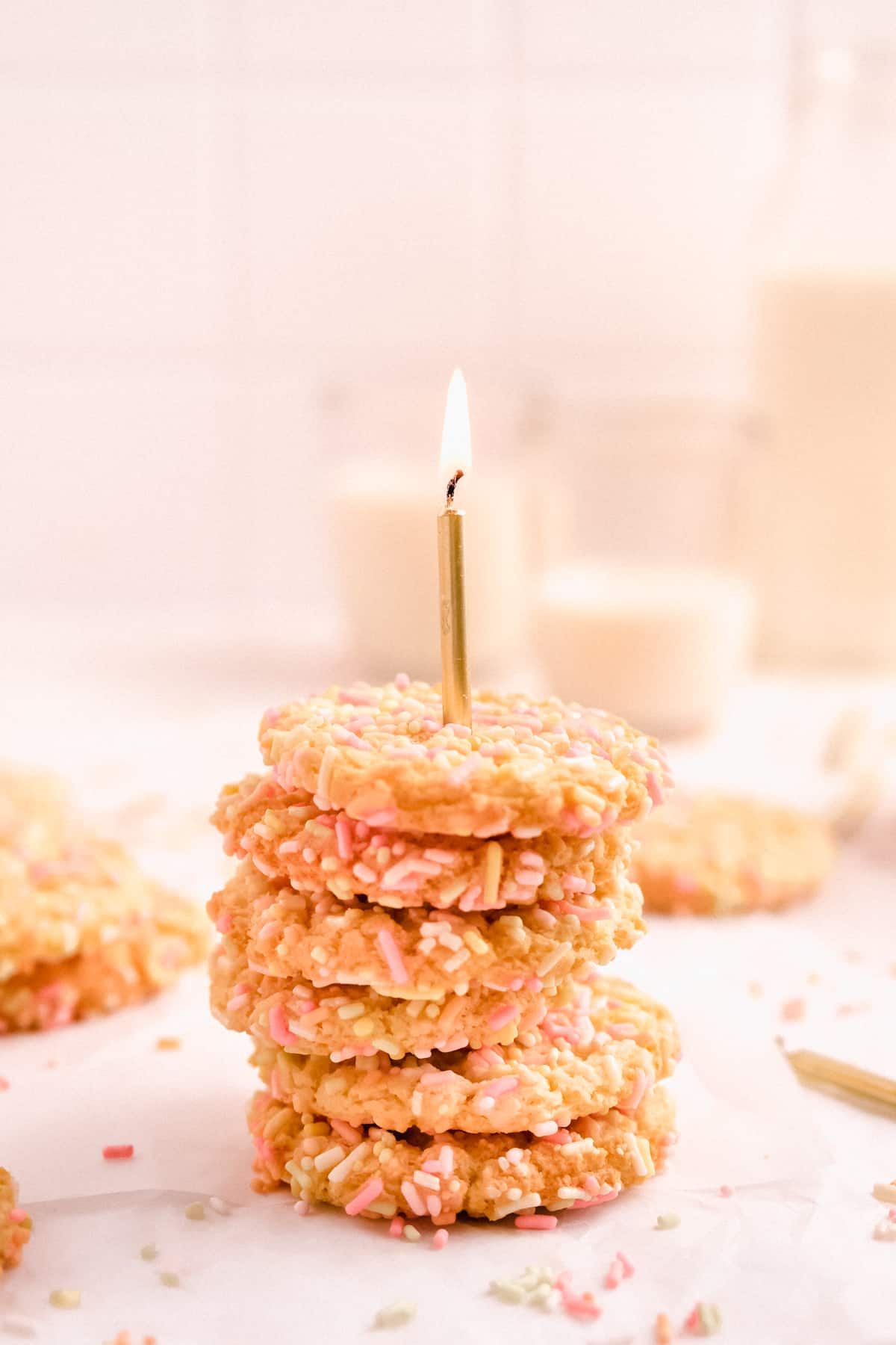 a stack of birthday cake sugar cookies on parchment covered in rainbow sprinkles with a lit birthday candle stuck in it with glasses of milk in the background