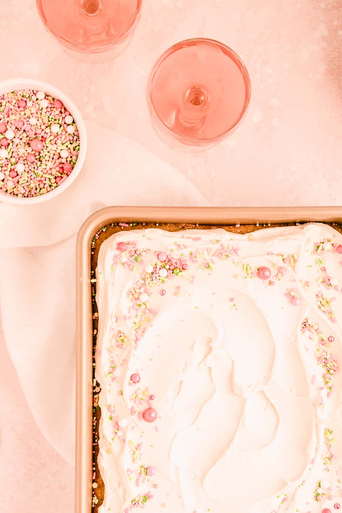 """easy vanilla sheet cake with vanilla buttercream and sprinkles on top in a 9"""" x 13"""" pan with glasses of rose and a bowl of sprinkles"""