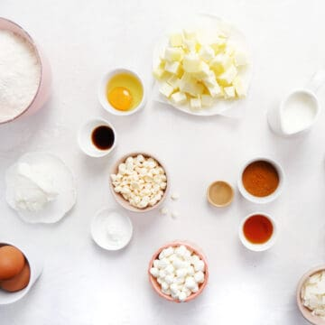 various ingredients used for baking in pink and white bowls on a white surface