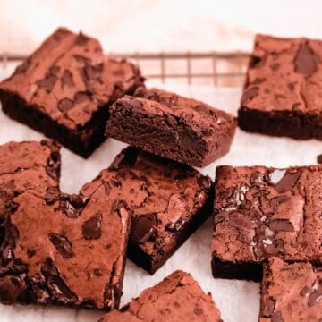 cut squares of fudgy gluten free brownies scattered on a wire cooling rack with parchment