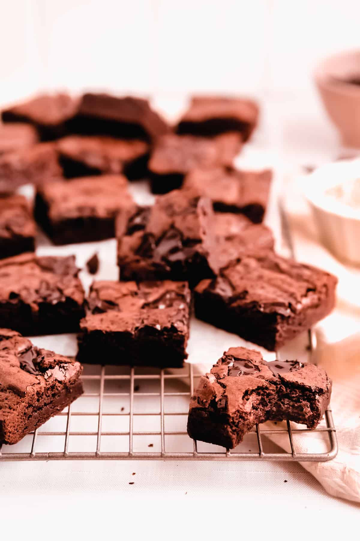 cut squares of fudgy gluten free brownies scattered on a wire cooling rack