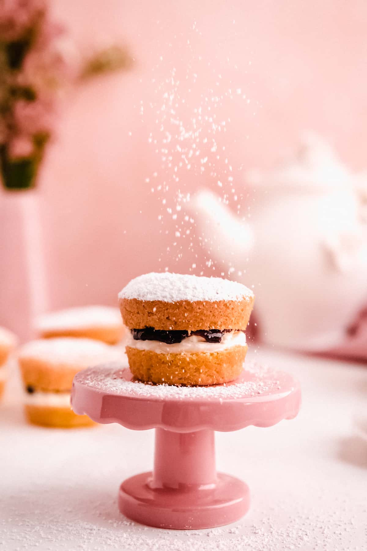 mini victoria sponge cakes filled with jam from above with powdered sugar falling on top of a mini cake plate with a teapot in the background