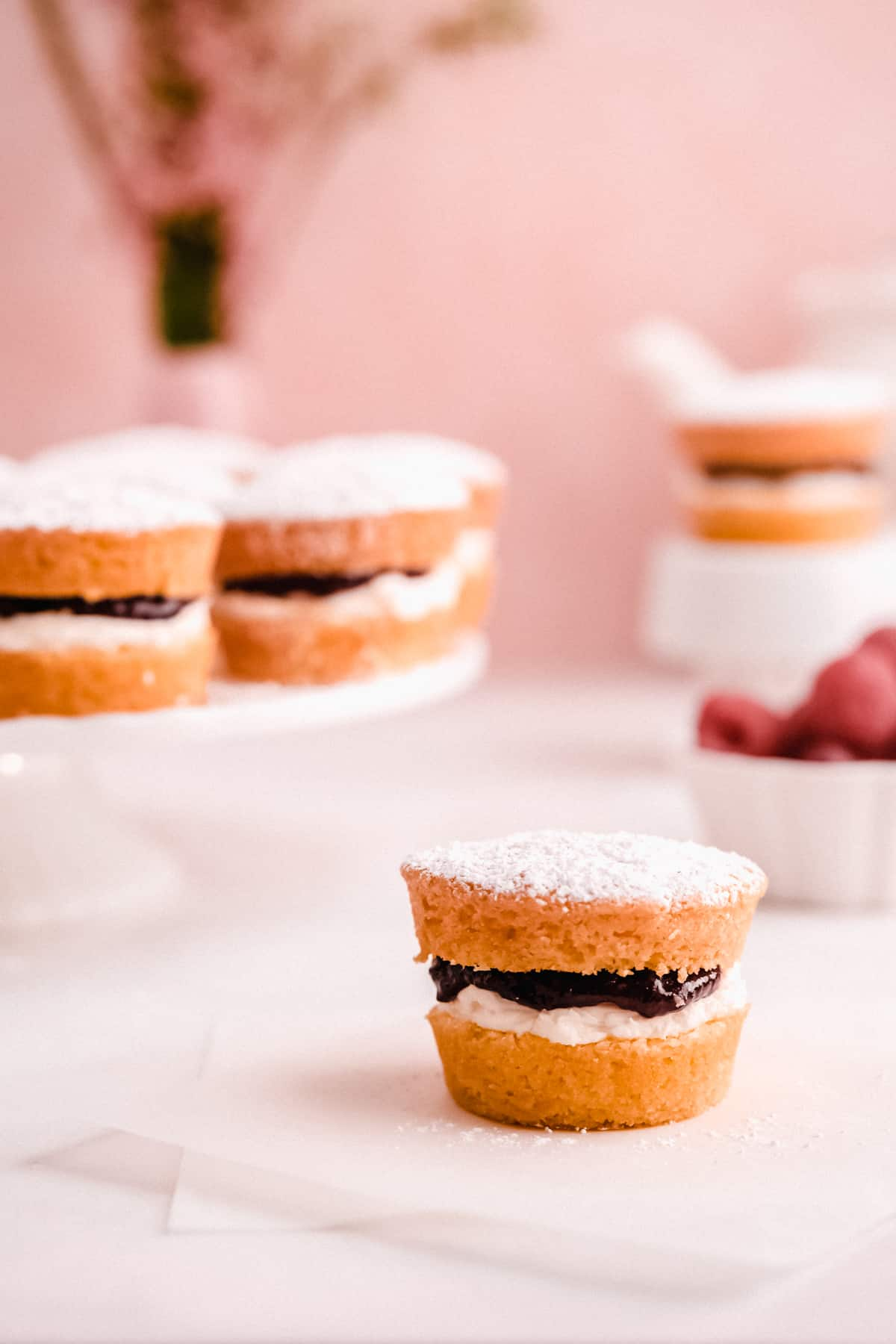 mini victoria sponge cakes filled with jam on a table and cake plate with raspberries and a teapot in the background