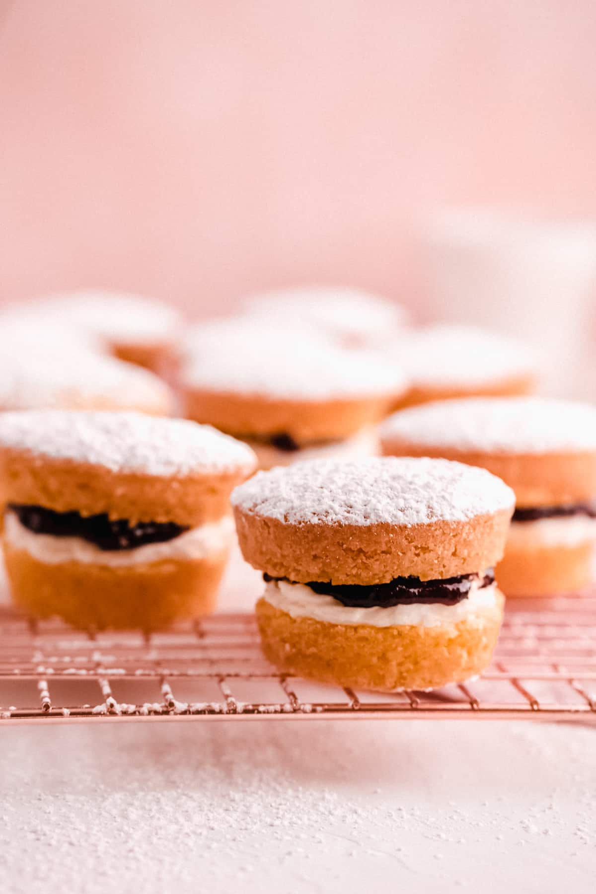 mini victoria sponge cakes filled with jam on a wire cooling rack