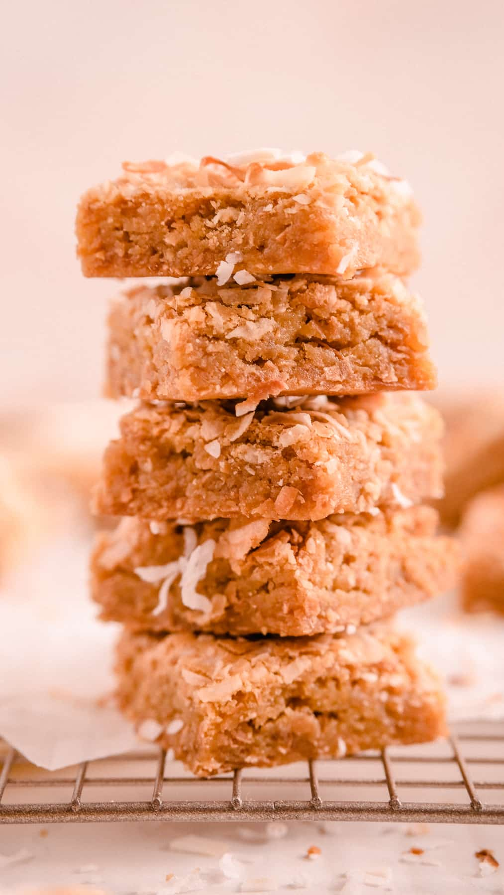 a stack of coconut butterscotch cookie bars on a wire rack