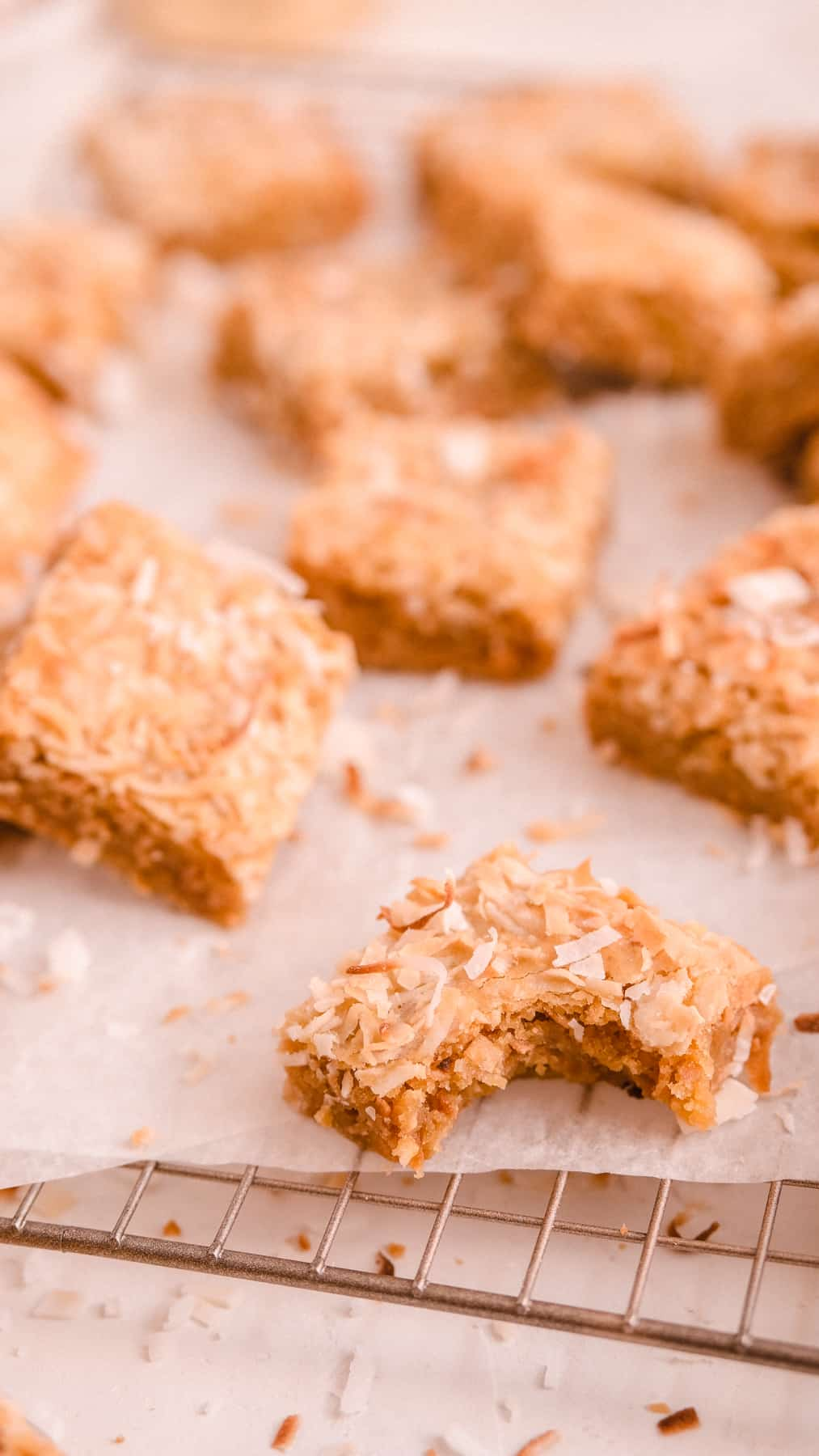 coconut butterscotch cookie bars on a wire rack with a bite out of one