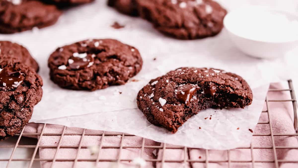 double chocolate chip cookies on a wire rack and parchment with a bite out of one