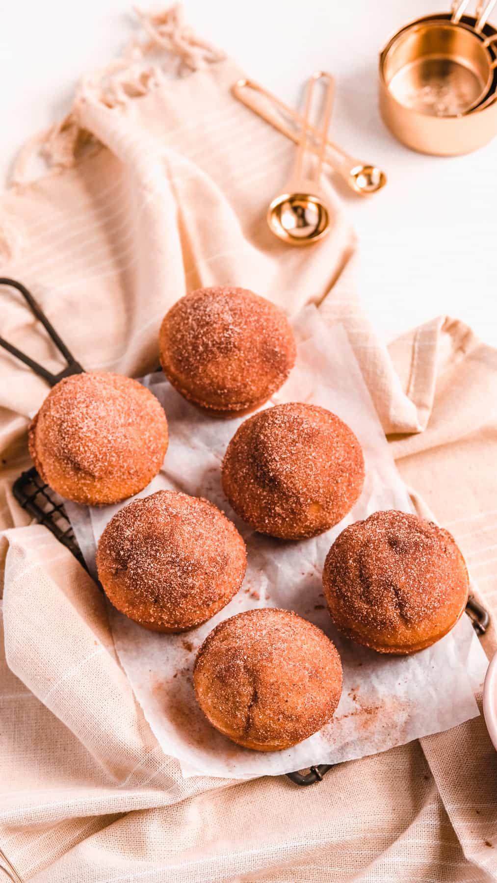Cinnamon Donut Muffins on a wire rack with baking utensils around them