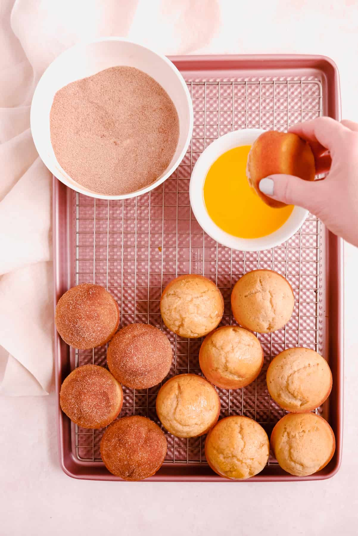 Cinnamon Donut Muffins on a cooling rack with butter and cinnamon and sugar