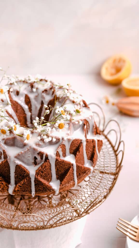 lemon bundt cake with lemon glaze and fresh flowers on a gold cake plate