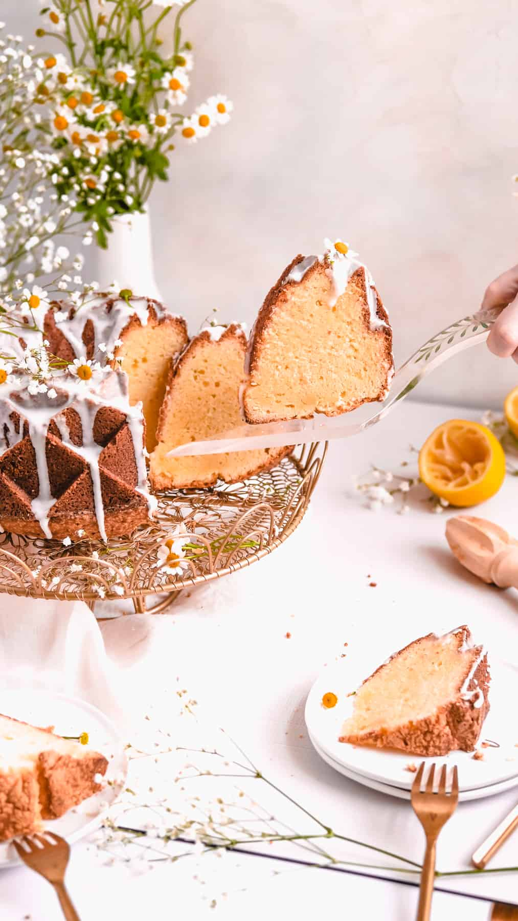 lemon bundt cake on a gold cake plate with lemons