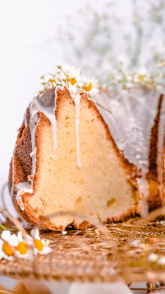 a cut lemon bundt cake with lemon glaze and fresh flowers on a gold wire cake plate