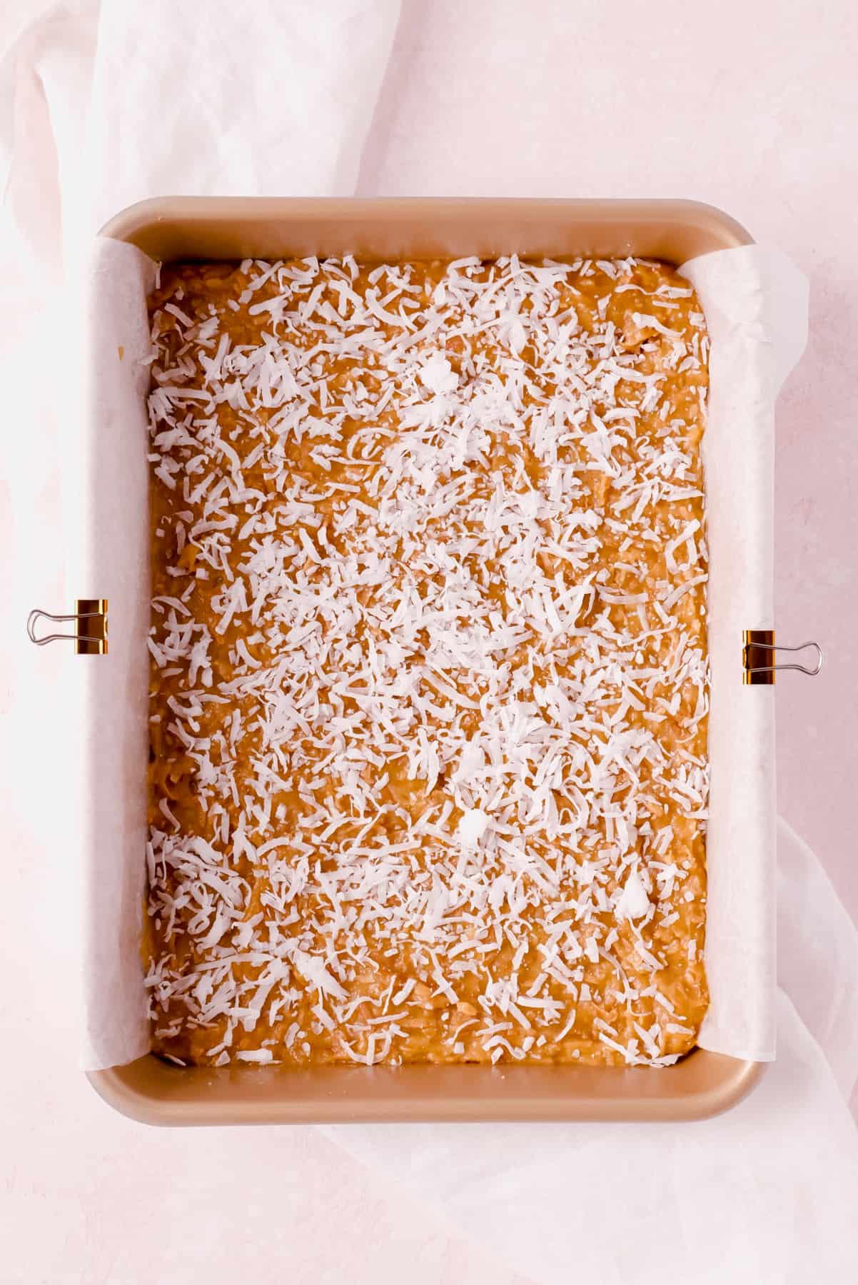"""unbaked coconut butterscotch bars in a 9""""x13"""" pan"""
