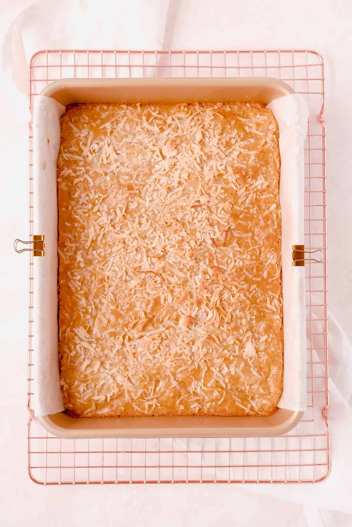 """coconut butterscotch bars in a 9""""x13"""" pan on a wire rack"""