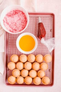 mini donut muffins with strawberry sugar and jam on a cooling rack