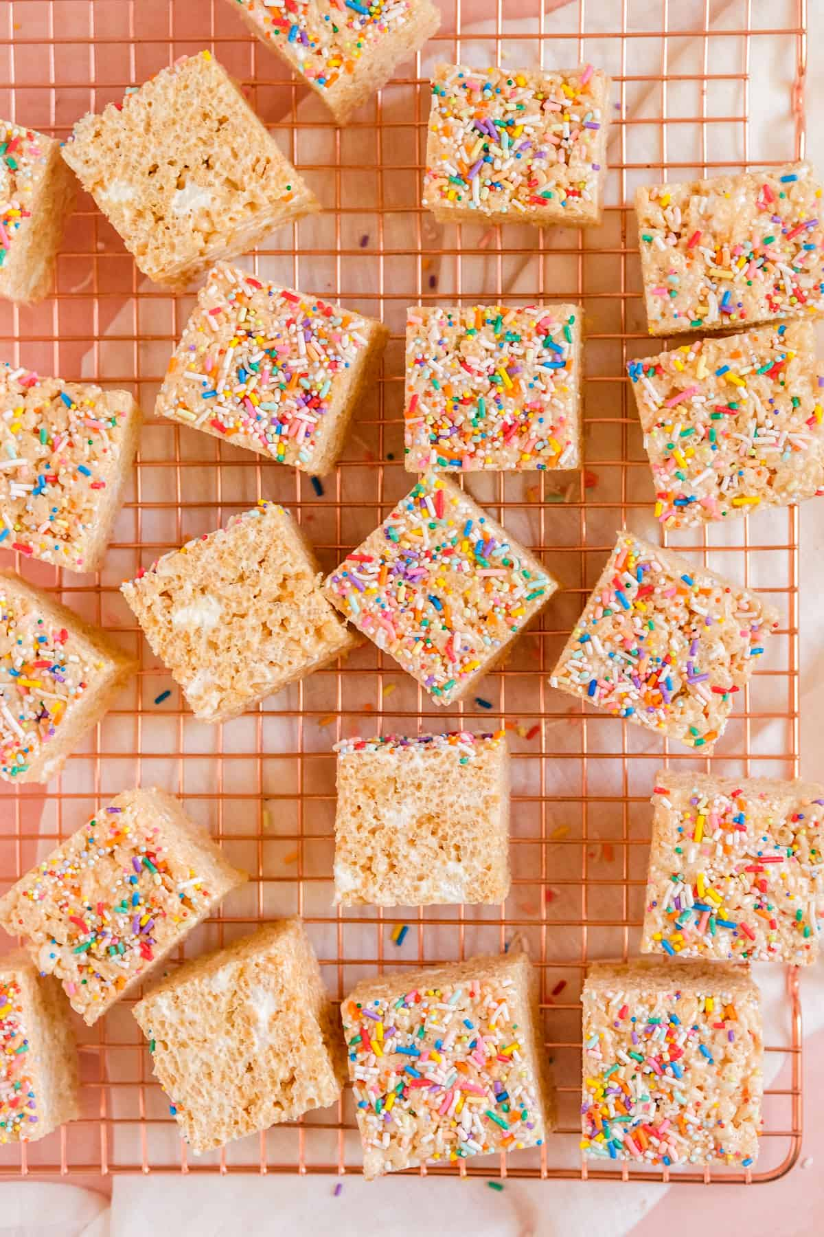 Brown Butter Rice Krispie Treats on a wire rack with sprinkles on top and some on the sides