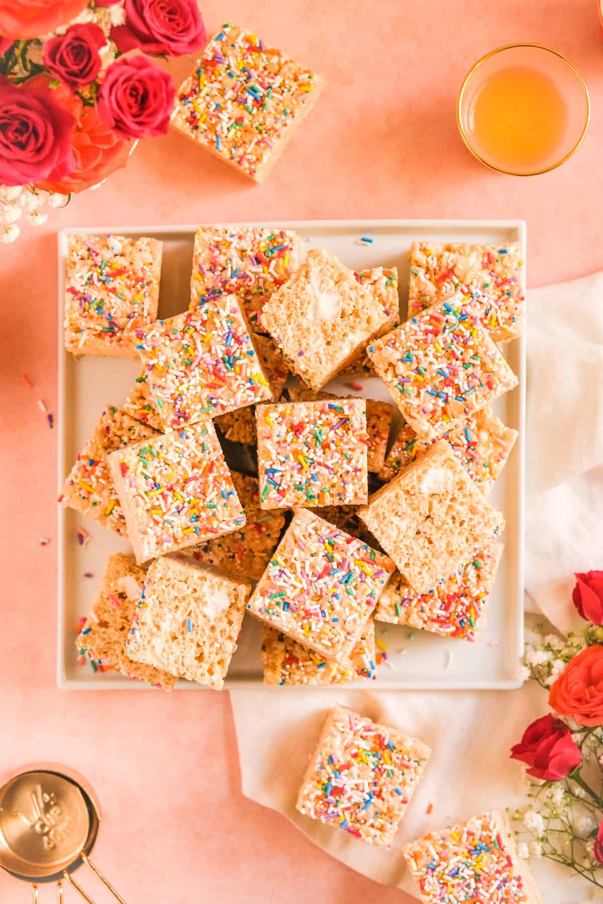 Brown Butter Rice Krispie Treats stacked on a plate with a glass of orange juice, measuring bags, and flowers on the table
