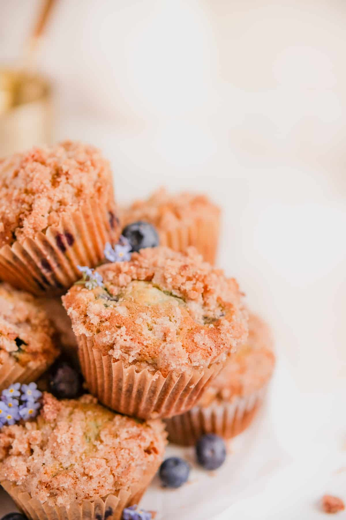 a close up of blueberry muffins with cinnamon streusel stacked up on a plate with forget me nots and blueberries on the plate
