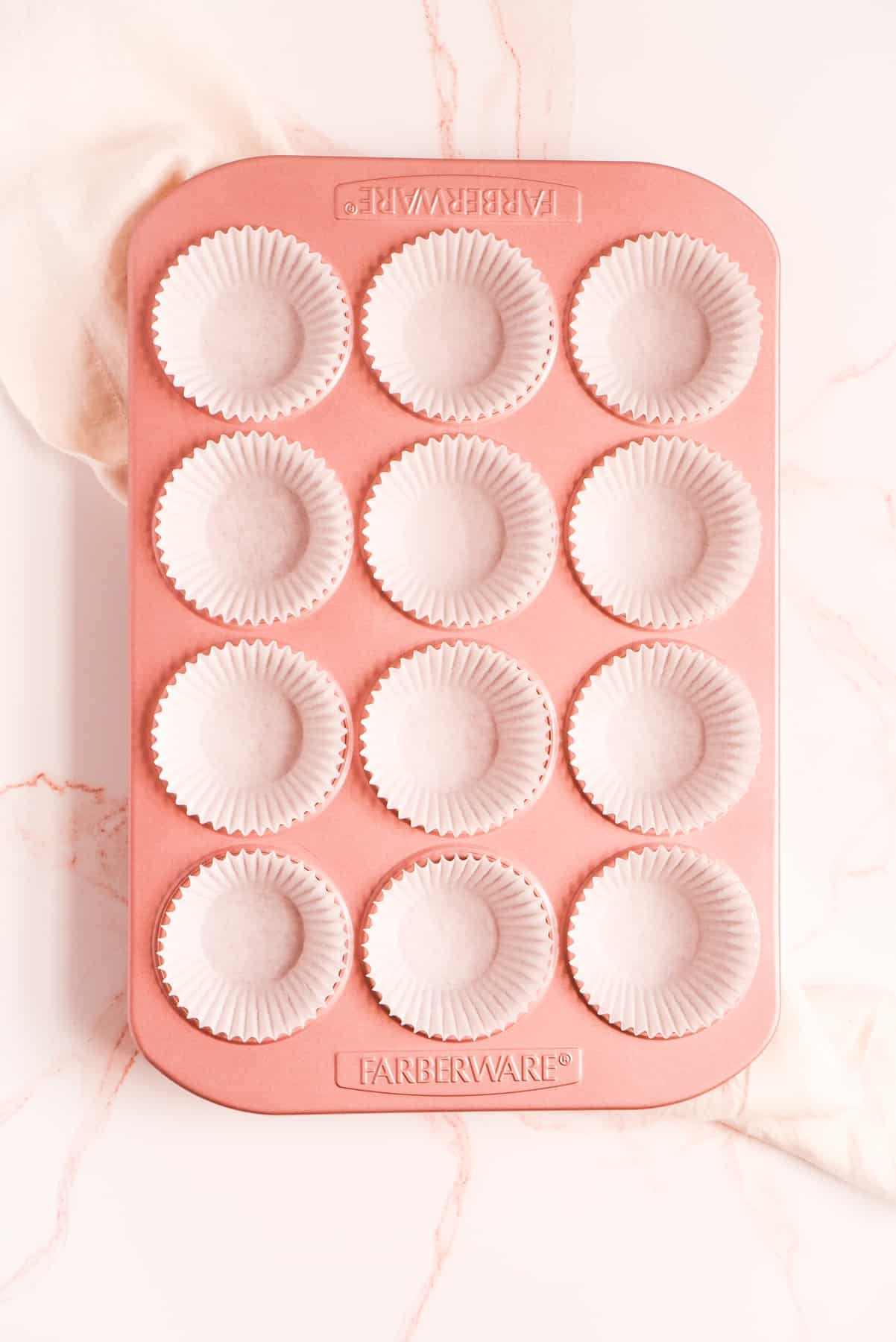 a pink muffin pan lined with white paper cups