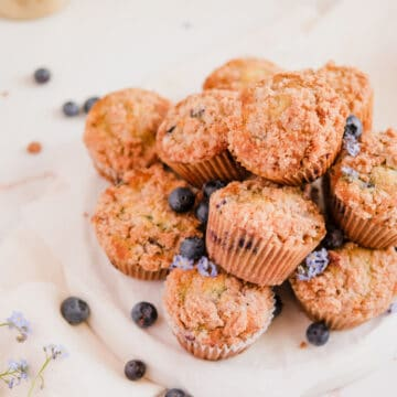 blueberry muffins with cinnamon streusel stacked up on a plate