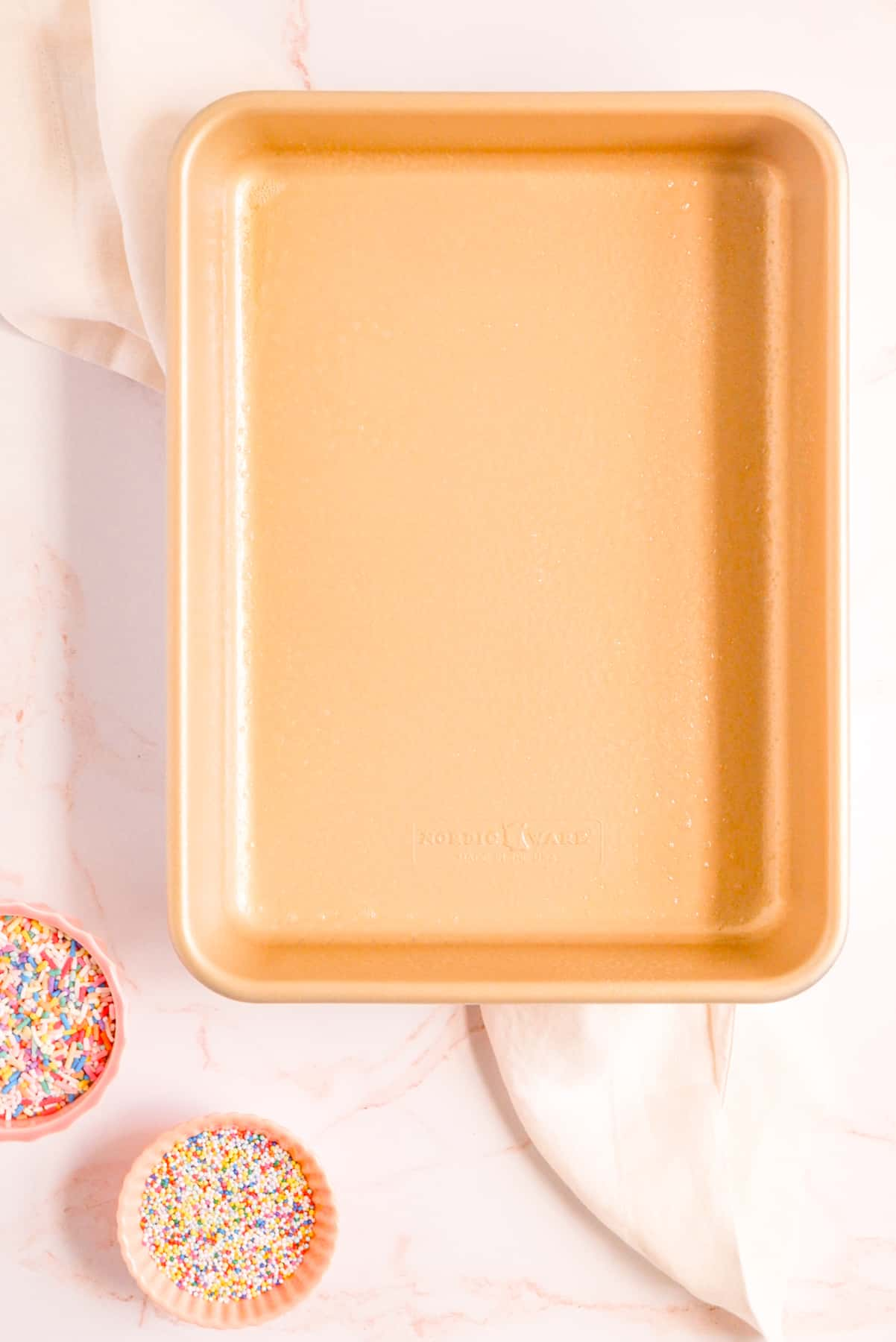 """a greased gold 9"""" x 13"""" pan with sprinkles in a bowl on the side"""