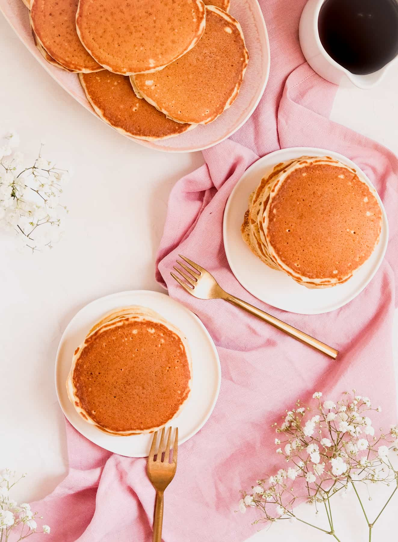 two stacks of buttermilk pancakes on a white plate with a fork