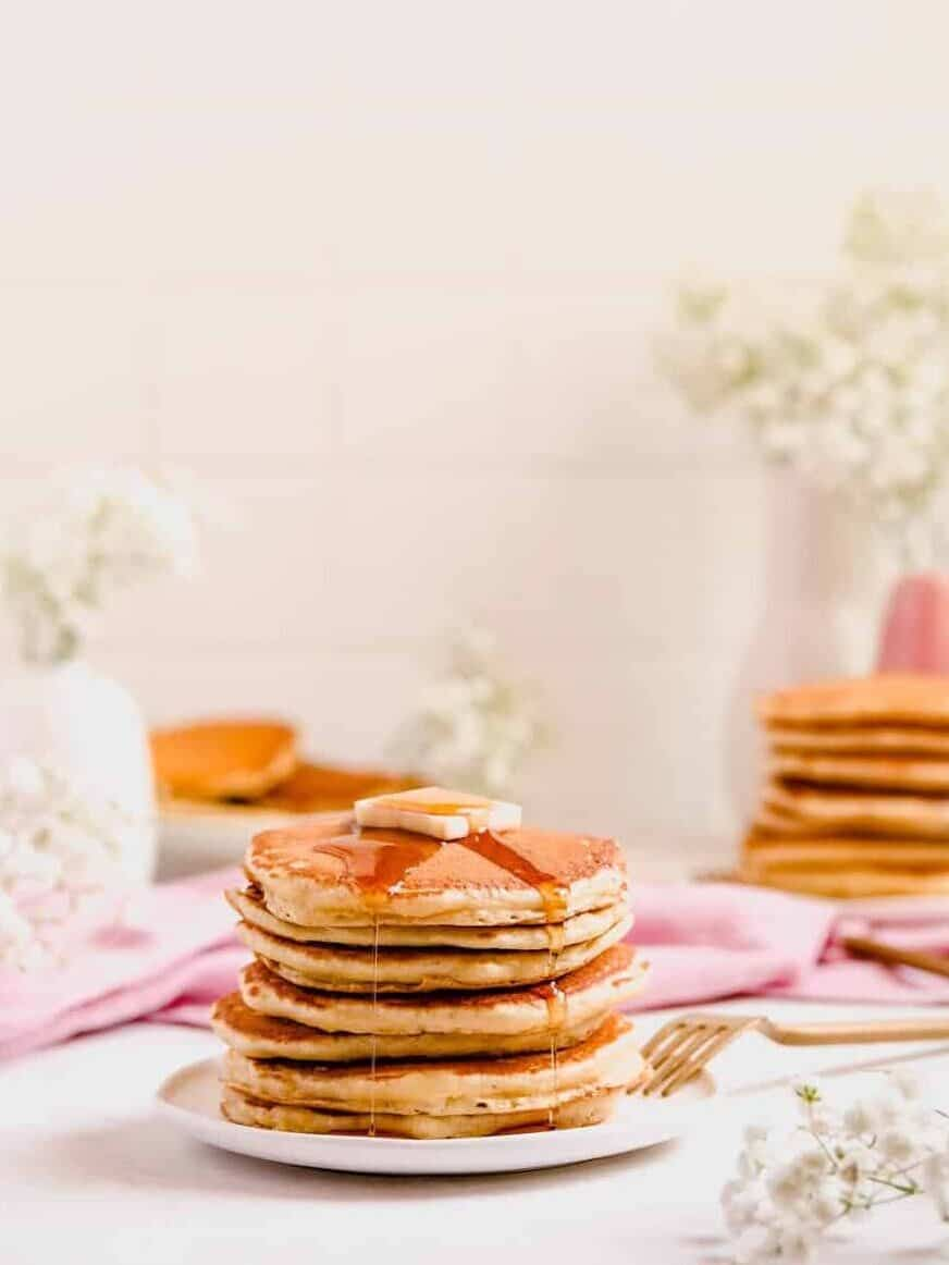 a stack of buttermilk pancakes with butter and syrup on them