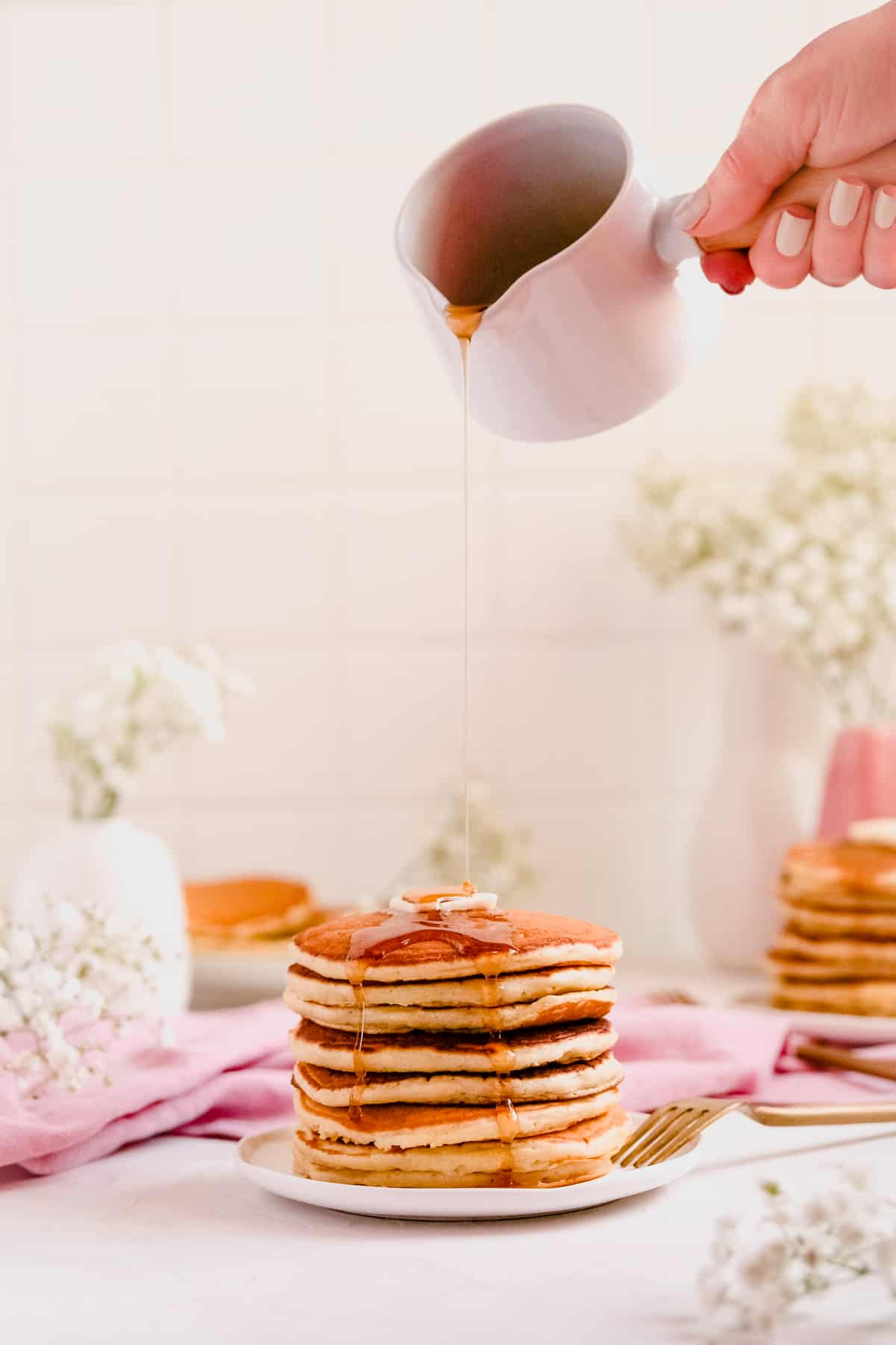 a stack of buttermilk pancakes with butter and syrup being poured on top
