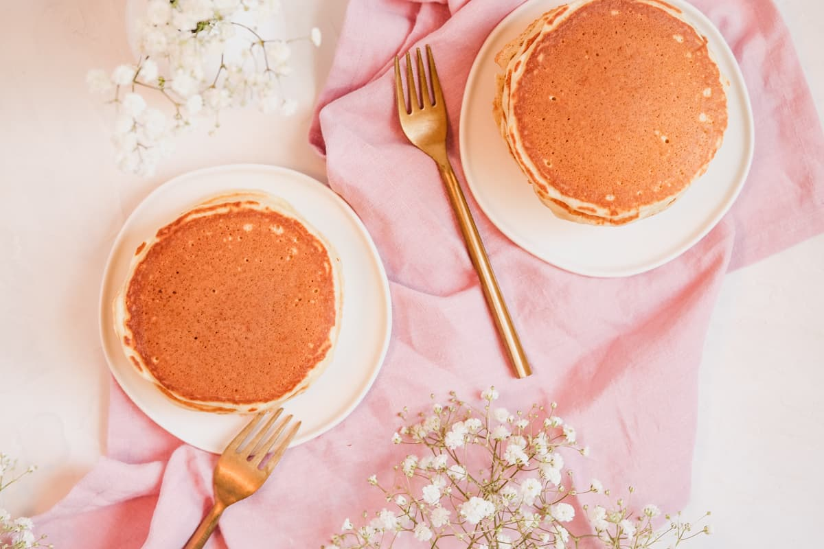 two plates of buttermilk pancakes on white plates with some flowers on the table