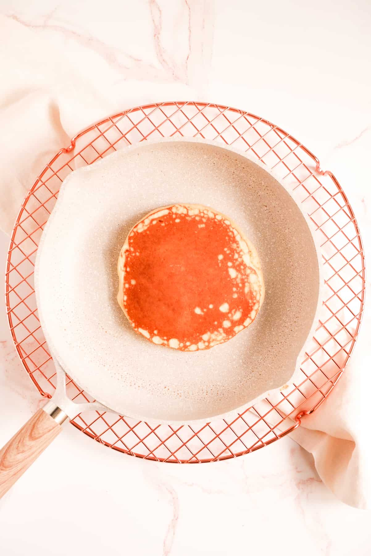 a buttermilk pancake cooking in a pan on a wire rack