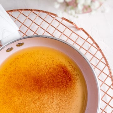 browned butter in a pink pan on a copper wire rack with flowers on the table