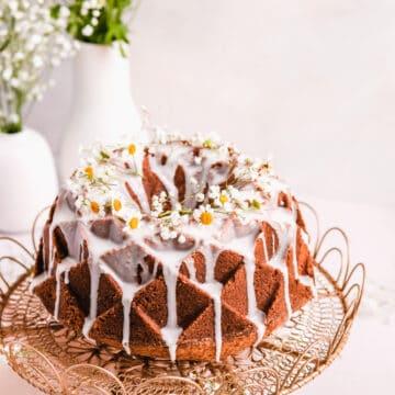 lemon bundt cake with lemon glaze and fresh flowers on a gold cake plate