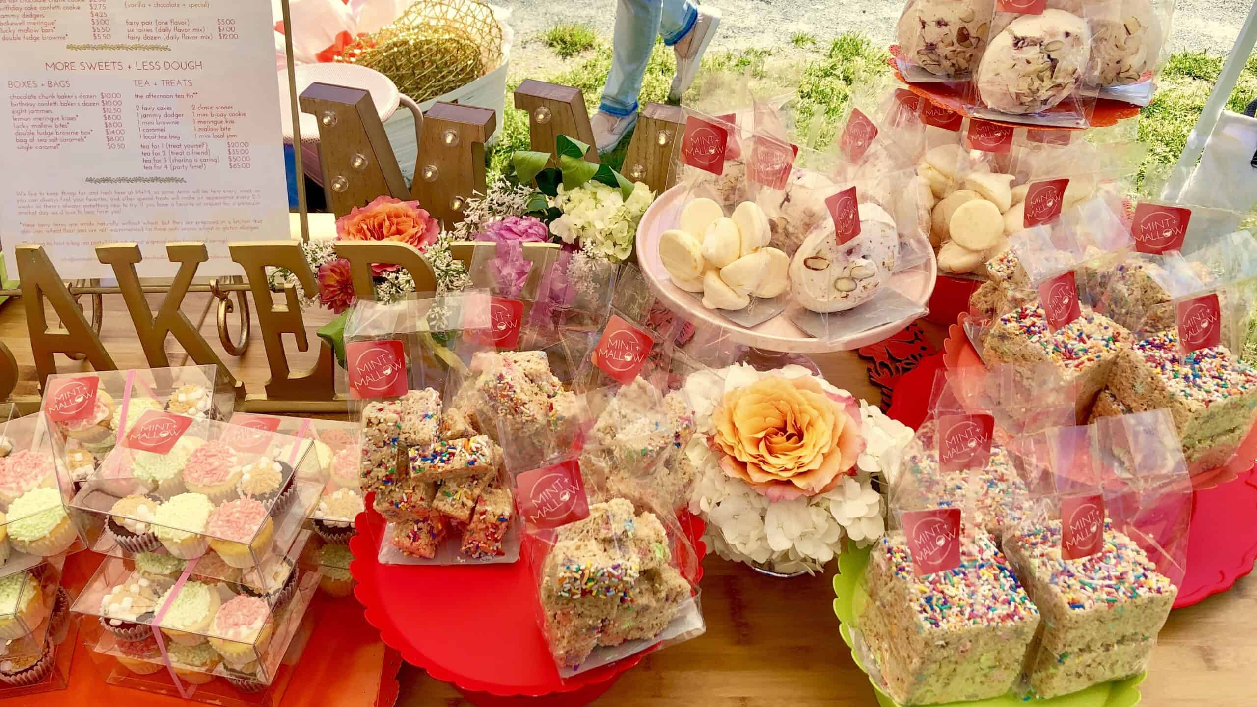 bags of meringues, cupcakes, and rice krispies on a table with pink trays and flowers in the background