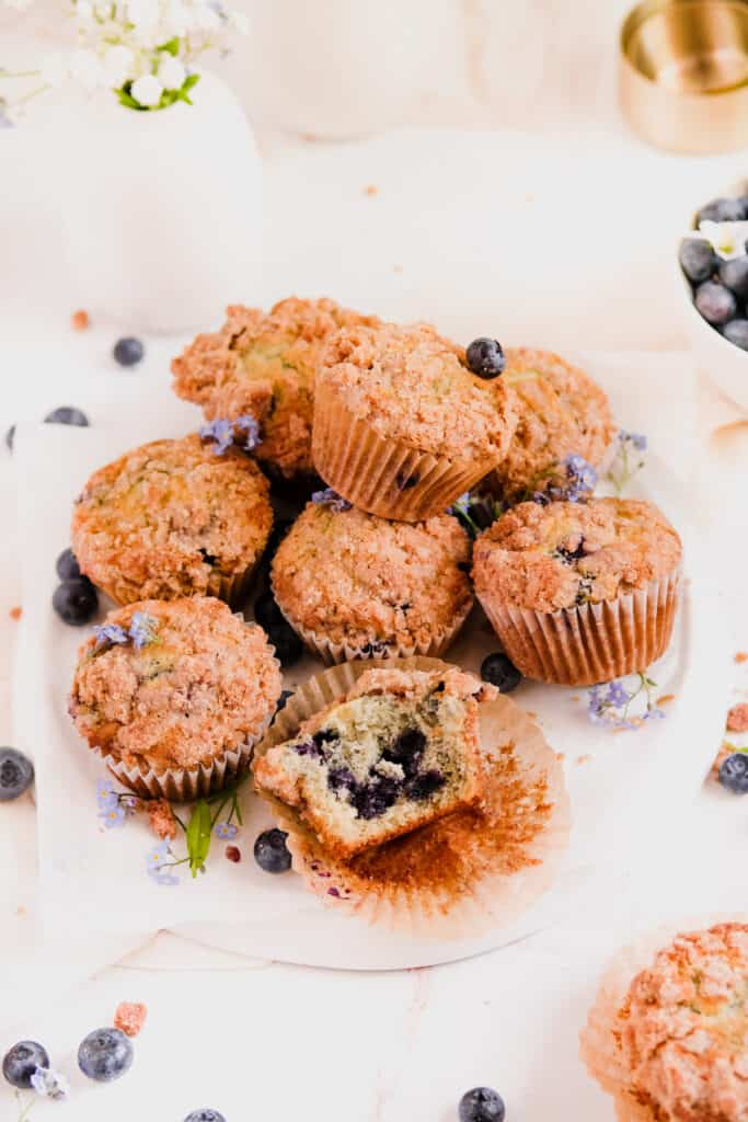 blueberry muffins with cinnamon streusel stacked up on a plate with forget me nots and blueberries on the plate
