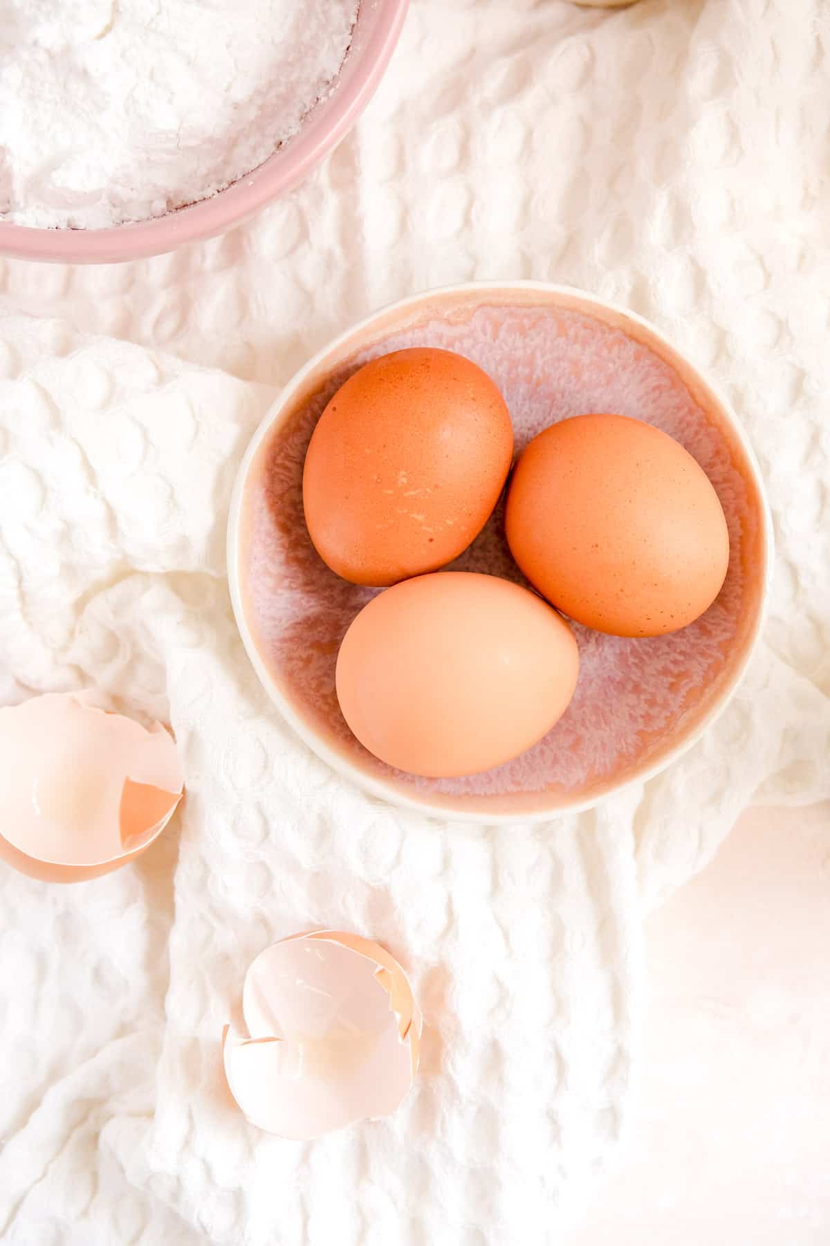 a bowl of 3 brown eggs with cracked egg shells on the side.