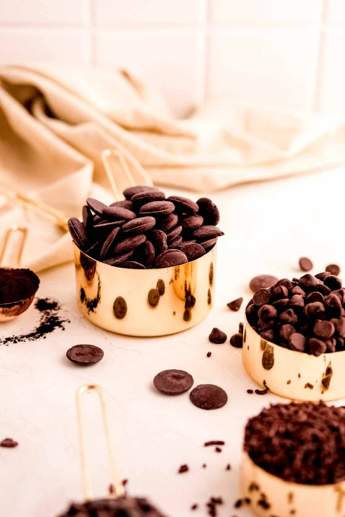 gold measuring cups piled high with chocolate ingredients.