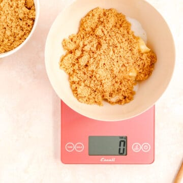 a red scale at 0 grams with a bowl filled with sugar and butter on top.