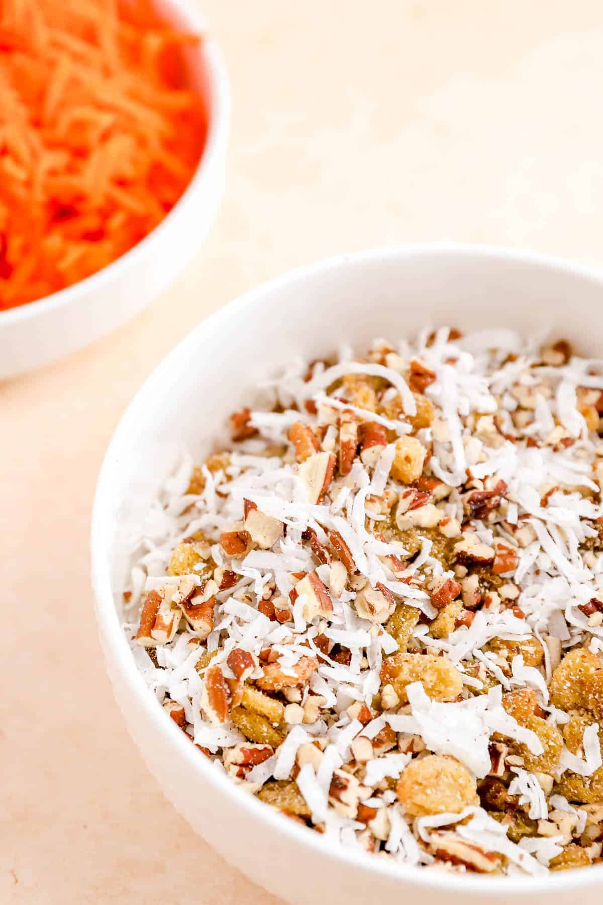 a blend of chopped pecans, golden raisins, and shredded coconut in a small bowl.