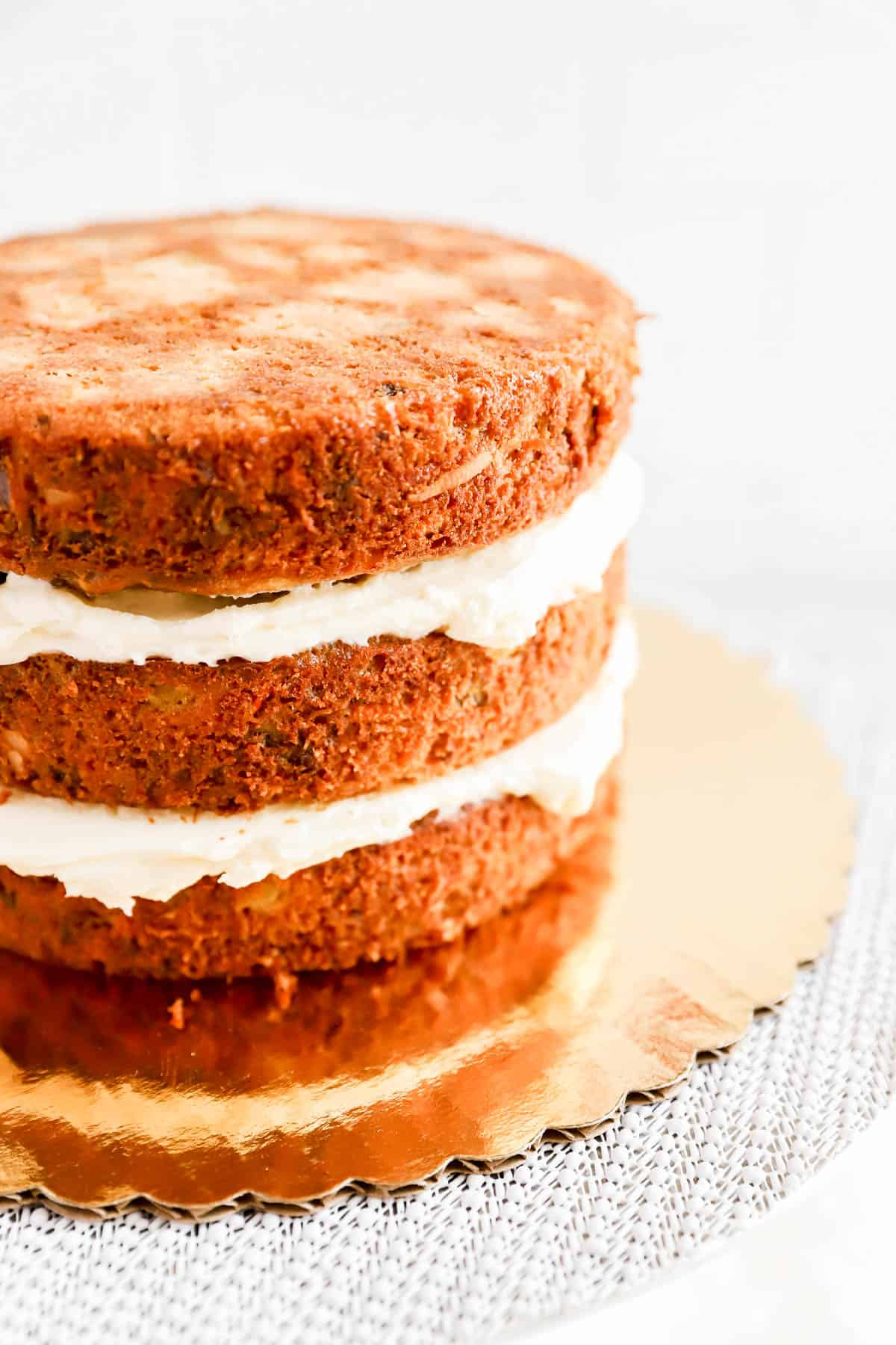 3 baked round carrot cake layers stacked and filled with cream cheese frosting.